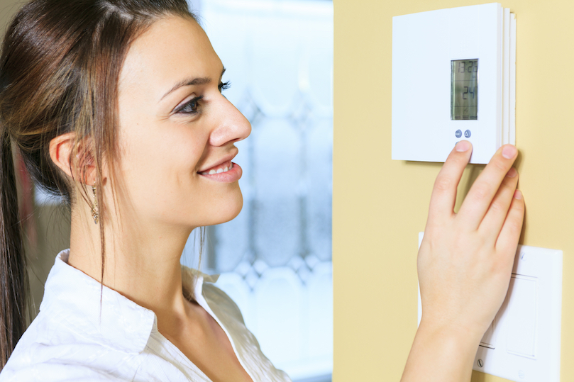 young-lady-adjusting-thermostat